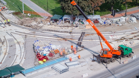 Installing concrete plates by crane at road construction site timelapse. Industrial workers with hardhats and uniform. Aerial top view. Reconstruction of tram tracks on intersection