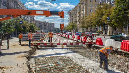 Orange construction telescopic mobile crane moving small pedestrian bridge timelapse. Industrial workers with hardhats and uniform. Reconstruction of tram tracks in the city street