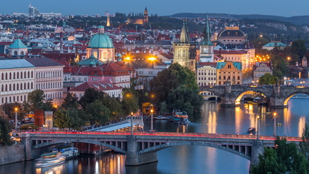 Aerial evening view of the Vltava River and illuminated bridges with traffic day to night transition timelapse, Prague. Towers and spires. Boats amd ship floating on water. Top view from Hanavsky pavilion