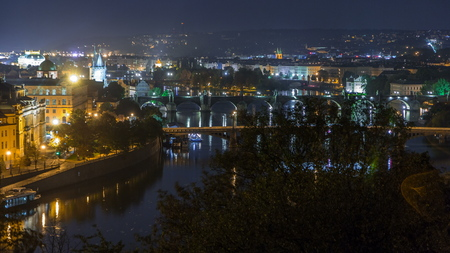 Aerial night view of the Vltava River and illuminated bridges with traffic and spires timelapse, Prague. Boats amd ship floating on water. Top view from metronom