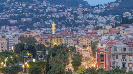 Evening aerial panorama of Nice day to night transition timelapse, France. Lighted Old Town little streets and Massena square after sunset. Traffic on the road Imagens