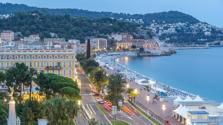 Evening aerial panorama of Nice day to night transition timelapse, France. Lighted Old Town little streets and waterfront after sunset. Traffic on the road Imagens