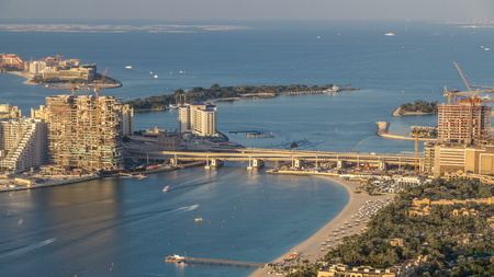 Aerial view of bridge to Palm Jumeirah Island timelapse. Evening top view with villas, hotels and yachts. Some buildings are under construction