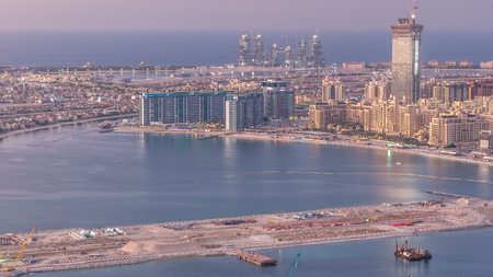 Aerial view of Palm Jumeirah Island day to night transition timelapse. Evening top view with illuminated villas, hotels and yachts. Construction process of new cruise terminal