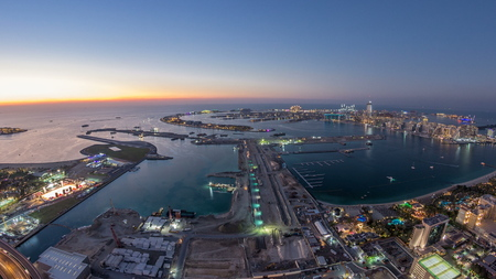 Aerial sunset view of Palm Jumeirah Island day to night transition timelapse. Evening top view with illuminated villas, hotels and yachts. Construction process of new cruise terminal Imagens