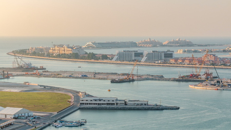 Aerial view of Palm Jumeirah Island timelapse. Evening top view with villas, hotels and yachts. Construction process of new cruise terminal