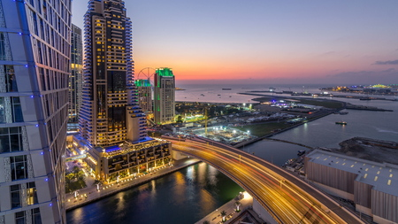 JBR and Dubai marina after sunset aerial day to night transition timelapse. Modern towers and skyscrapers, traffic on the bridge, yachts and boats floating on canal