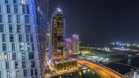 JBR and Dubai marina aerial night timelapse. Illuminated modern towers and skyscrapers, traffic on the bridge, yachts and boats floating on canal 写真素材