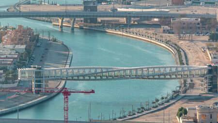 Dubai water canal with footbridge during sunset aerial timelapse from Downtown skyscrapers rooftop. Floating boats and construction site with cranes