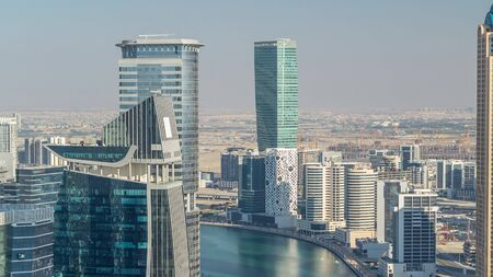 Aerial skyline of Dubais business bay with skyscrapers timelapse before sunset. Modern towers and canal from above