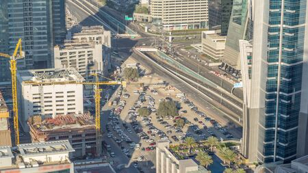 Aerial view of traffic on Business Bay with parking timelapse. Big modern city with skyscrapers and construction site. Downtown Dubai, United Arab Emirates.
