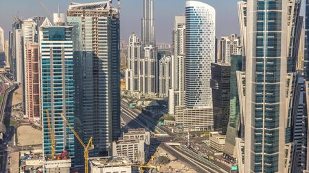 Aerial view of towers in Business Bay with traffic on the road timelapse. Big modern city with skyscrapers and construction site. Downtown Dubai, United Arab Emirates.