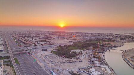 Panorama and aerial view of coastline Dubai at sunset timelapse, United Arab Emirates. Dubai water canal, sheikh zayed road, houses and villas from above Banco de Imagens