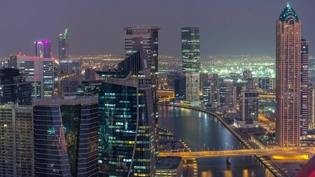 Aerial skyline of Dubais business bay with skyscrapers day to night transition timelapse. Illuminated modern towers and canal from above