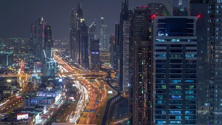 Aerial view to skyscrapers on Dubai downtown and Sheikh Zayed road night timelapse, Dubai, United Arab Emirates. Modern towers and evening traffic on highway Banco de Imagens