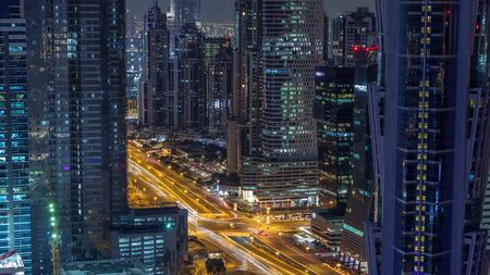 Aerial view of towers in Business Bay with traffic on the road night timelapse. Big modern city with skyscrapers and construction site. Downtown Dubai, United Arab Emirates. Banco de Imagens