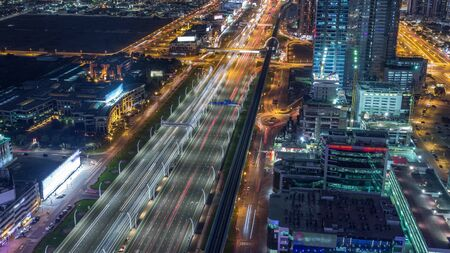 Aerial view to traffic on Sheikh Zayed road and skyscrapers on Dubai downtown night timelapse, Dubai, United Arab Emirates. Modern towers and evening motion on highway