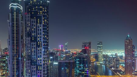 Aerial view of towers in Business Bay with water canal night timelapse. Big modern city with skyscrapers. Downtown Dubai, United Arab Emirates.