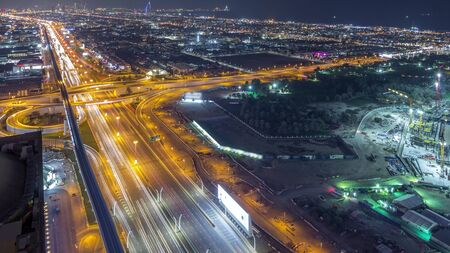 Aerial view to traffic on Sheikh Zayed road and intersection night timelapse, Dubai, United Arab Emirates. Metro line and houses Banco de Imagens