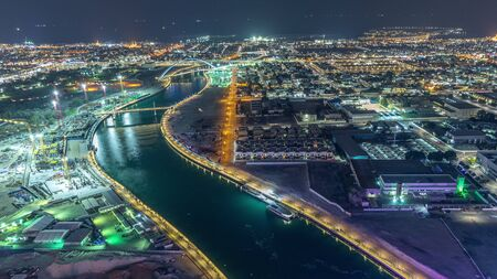 Dubai water canal with footbridge aerial night timelapse from Downtown skyscrapers rooftop. Illuminated waterfront. Floating boats and construction site with cranes Banco de Imagens