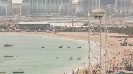 Aerial view of beach and tourists walking and sunbathing on holiday in JBR timelapse in Dubai, UAE. Waterfront with many activities and attractions, shops and restaurants