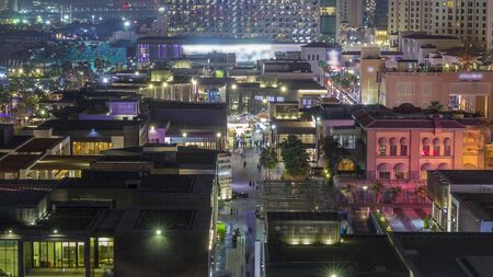 Aerial view of beach and tourists walking in JBR with illuminated buildings on background night timelapse in Dubai, UAE. Waterfront with many activities and attractions, shops and restaurants Banco de Imagens