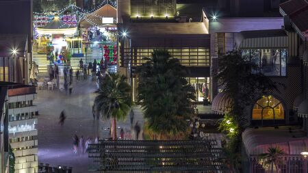 Aerial view of tourists walking in JBR with illuminated buildings night timelapse in Dubai, UAE. Waterfront with many activities and attractions, shops and restaurants Banco de Imagens