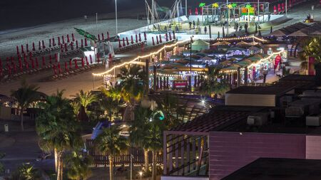 Aerial view of beach and tourists walking in JBR night timelapse in Dubai, UAE. Waterfront with many activities and attractions, shops and restaurants Banco de Imagens