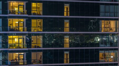 Glowing apartment windows at night in glass skyscraper timelapse. Warm light and motion inside. Lights reflected from surface. Pan down
