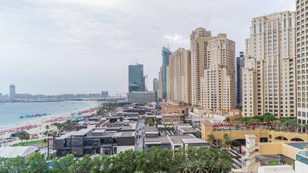 Aerial view of beach skyline and tourists walking in JBR timelapse in Dubai, UAE. Skyscrapers on a background. Waterfront with many activities and attractions, shops and restaurants 免版税图像
