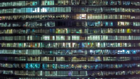 Working evening in glass office building with numerous offices with glass walls and illuminated windows timelapse. People sitting at desks. Pan up