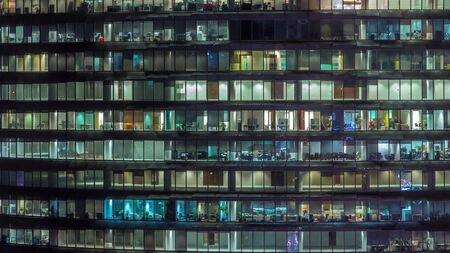 Working evening in glass office building with numerous offices with glass walls and illuminated windows timelapse. People sitting at desks. Pan right Banco de Imagens