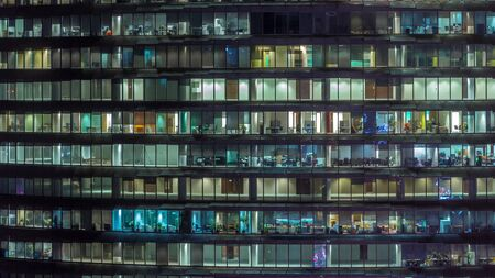 Working evening in glass office building with numerous offices with glass walls and illuminated windows timelapse. People sitting at desks