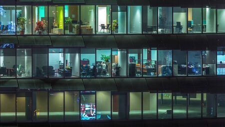 Working evening in glass office building with numerous offices with glass walls and illuminated windows timelapse. People sitting at desks. Pan down