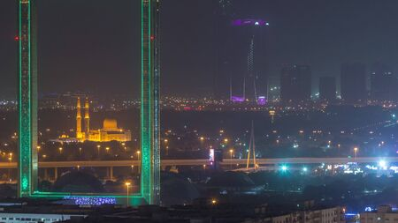 Dubai Frame with Zabeel Masjid mosque illuminated at night timelapse. Aerial view from above during sand storm. The Frame is an architectural landmark in Zabeel Park.