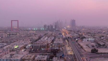 Dubai cityscape during sand storm day to night transition timelapse, aerial view of skyscrapers and traffic on the road from Zabeel district, United Arab Emirates