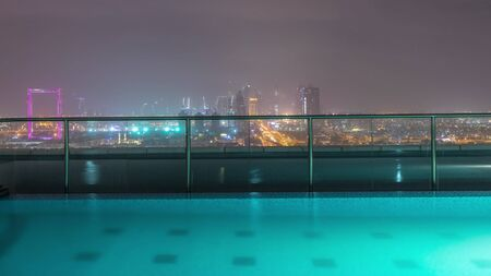 Dubai cityscape during sand storm night timelapse, aerial view of skyscrapers and illuminated swimming pool from Zabeel district, United Arab Emirates Banco de Imagens