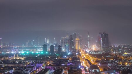 Dubai downtown cityscape during sand storm night timelapse, aerial view of skyscrapers and traffic on the road from Zabeel district, United Arab Emirates Banco de Imagens