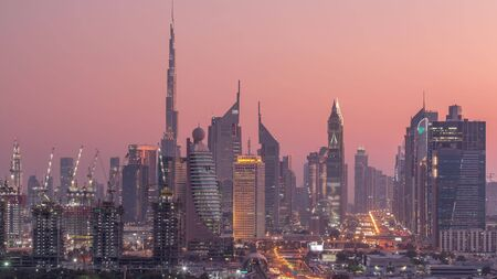 Dubai skyline after sunset with beautiful city center lights and Sheikh Zayed road traffic day to night transition timelapse. Illuminated towers and skyscrapers aerial view from zabeel district. Dubai, United Arab Emirates