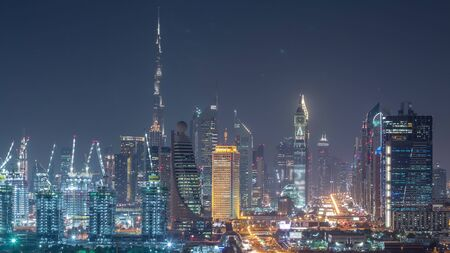 Dubai skyline with beautiful city center lights and Sheikh Zayed road traffic night timelapse. Illuminated towers and skyscrapers aerial view from zabeel district. Dubai, United Arab Emirates Banco de Imagens