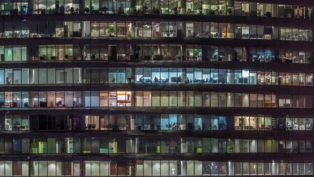 Working evening in glass business centre office building with numerous offices with glass walls and illuminated windows timelapse. People sitting at desks. Pan down Banco de Imagens