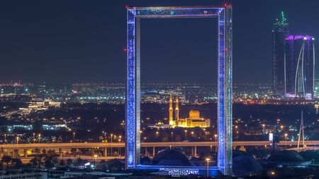 Dubai Frame with Zabeel Masjid mosque illuminated at night timelapse. Aerial view from above. The Frame is an architectural landmark in Zabeel Park. Banco de Imagens