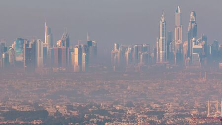 Dubai Marina and Jumeirah beach during sunrise with early morning fog timelapse in Dubai, United Arab Emirates. Aerial view from downtown with skyscrapers, villas and mosque Stock fotó