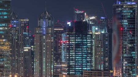 Dubai Marina and JLT aerial night timelapse top view of skyscrapers in Dubai, UAE. Modern towers and traffic on streets
