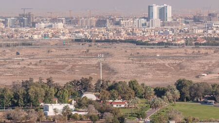 Aerial view to villas and houses near Golf course timelapse. Desert and construction site in Jumeirah village circle district. Warm evening light 免版税图像