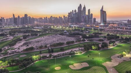 Jumeirah lake towers and Dubai Marina skyscrapers and golf course day to night transition timelapse, Dubai, United Arab Emirates. Aerial view from Greens district after sunset Stock fotó