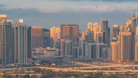 Jumeirah lake towers and Dubai Marina skyscrapers and golf course morning timelapse, Dubai, United Arab Emirates. Moving long shadows. Aerial view from Greens district. Green lawn and cloudy sky. Traffic on a highway