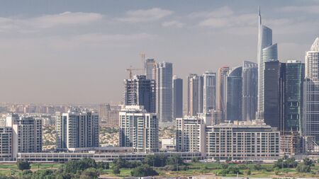 Jumeirah lake towers skyscrapers and golf course morning timelapse, Dubai, United Arab Emirates. Aerial view from Greens district. Green lawn and cloudy sky Stock fotó