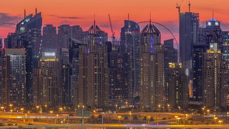 Dubai Marina skyscrapers and golf course day to night transition timelapse, Dubai, United Arab Emirates. Aerial view from Greens district after sunset Stock fotó