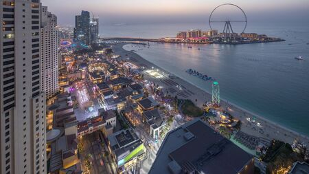 Waterfront overview Jumeirah Beach Residence JBR skyline aerial day to night transition timelapse with illuminated skyscrapers. Shops, restaurants and other entertainment from above Stock Photo